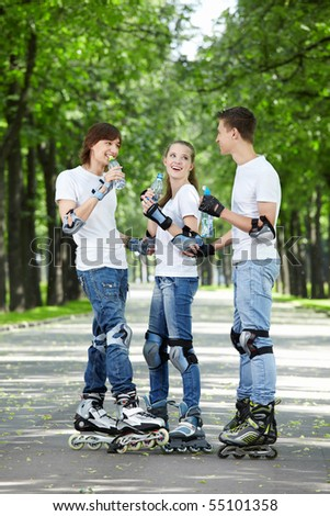 Three young people on rollers drink water - stock photo