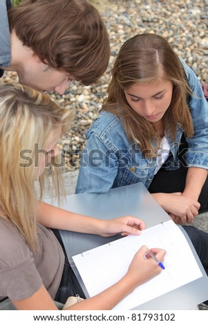Three young people, one of them writing in a binder on her lap. - stock photo