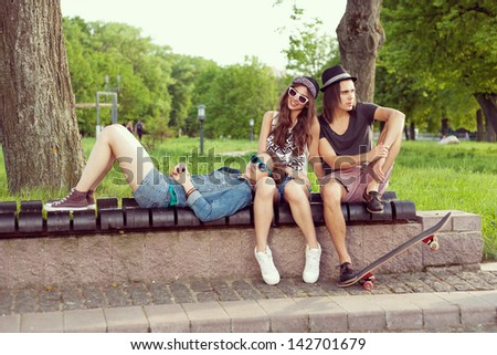 Three Young People Sitting Together On Park Bench. Outdoors - stock photo