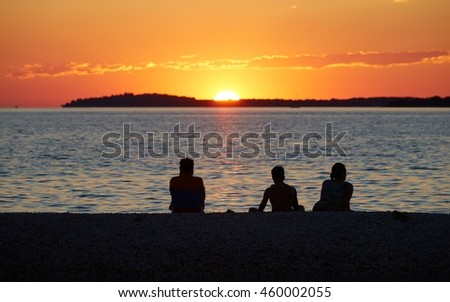 Three young people watching the sunset over Brioni islands in Pula, Croatia