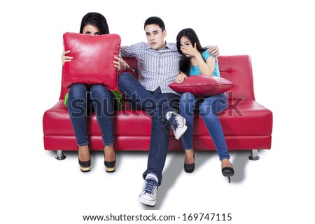 Three young people watching TV a horror movie and they are scared