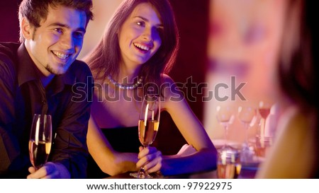 Three young people with champagne glasses at restaurant - stock photo