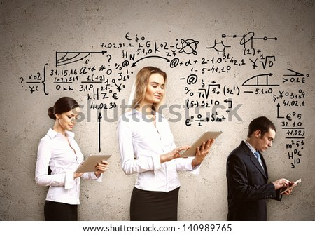 Three young people with tablet pc in hands against drawings at background - stock photo
