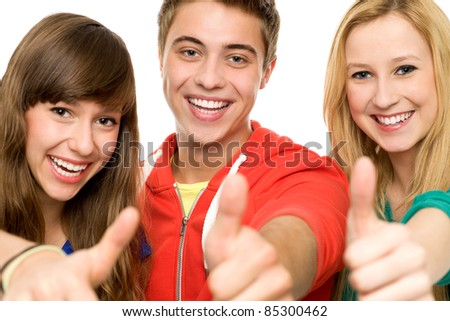 Three young people with thumbs up - stock photo