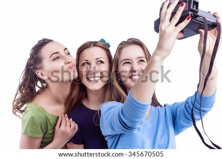 Three Young Positive Smiling Caucasian Ladies Making Self Photographs With Photocamera. Isolated Over White Background. Horizontal Image Orientation