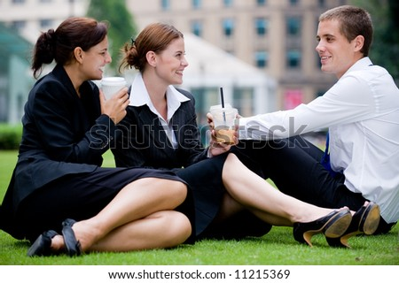 Three young professionals sitting outside in park having coffee break - stock photo