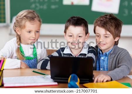 Three young schoolchildren, a pretty little girl and two boys, sitting together at a desk using a laptop computer in class - stock photo