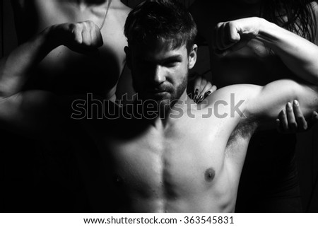 Three young sexy people of handsome bearded muscular macho man and two sensual attractive girls lovers with beautiful body and naked chest close to each other indoor, horizontal picture - stock photo