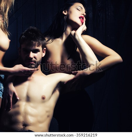 Three young sexy people of handsome bearded muscular macho man holding two sensual attractive girls lovers with beautiful body and naked chest close to each other indoor, square picture - stock photo