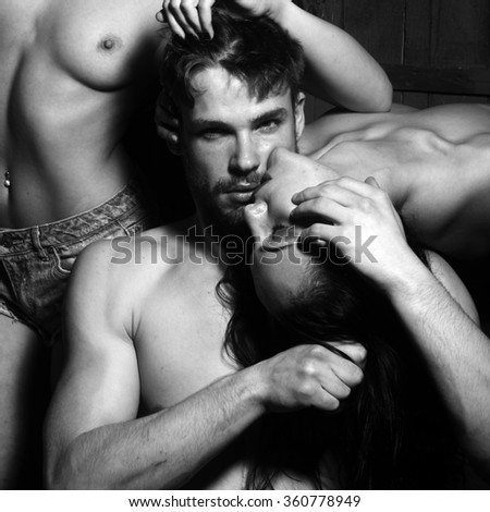 Three young sexy people of handsome bearded muscular macho man touching two sensual attractive girls lovers with beautiful body and naked chest close to each other indoor, square picture - stock photo