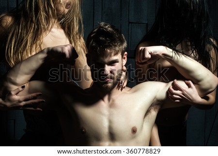 Three young sexy people of handsome strong bearded muscular macho man and two sensual attractive girls lovers with beautiful body and naked chest close to each other indoor, horizontal picture - stock photo