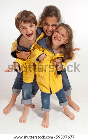 Three young siblings barefoot wearing jeans and yellow raincoats - stock photo