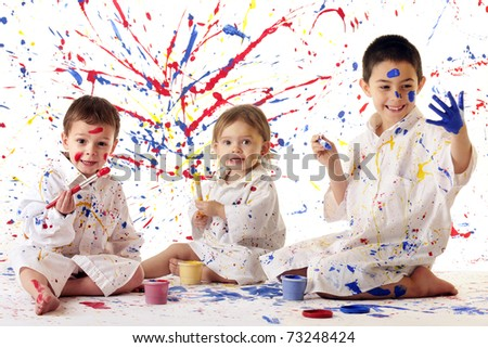 Three young siblings in white paint spattered smocks painting in primary colors on white. - stock photo