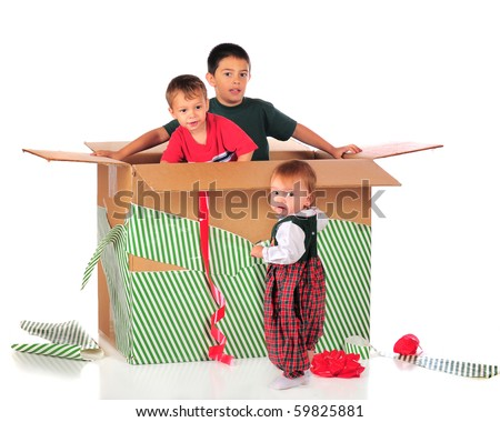 Three young siblings playing in the box of a giant Christmas gift.  Isolated on white. - stock photo