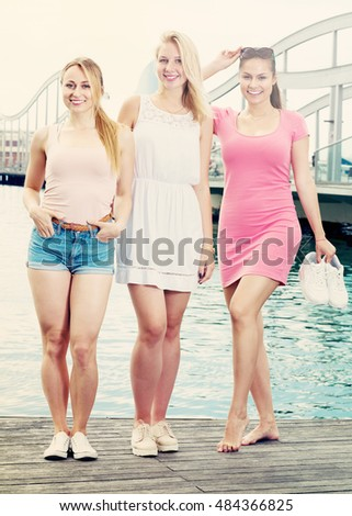 Three young smiling girls standing together on waterfront in town on summer day