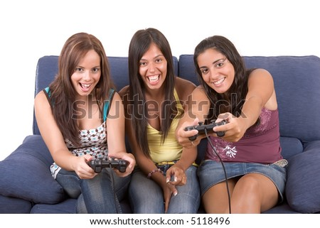 Three young smiling women are sitting on a blue couch and looks like playing video games. Two of them are holding video games controller pads - over a white background