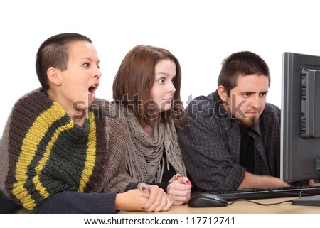 Three young surprised Caucasian people looking to computer