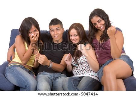 Three young woman and a man are sitting on a blue couch and looks like watching TV. They are very excited by what they see - over a white background