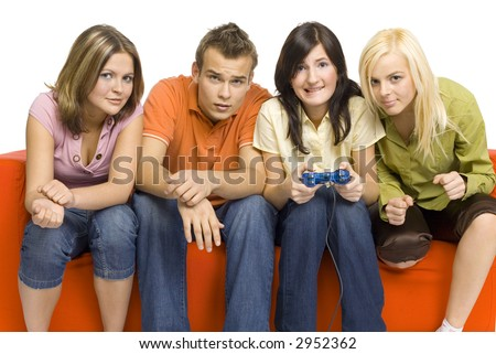Three young woman and a man are sitting on the orange couch and looks like playing video game. Woman is holding computer pad.  Isolated on white in studio. - stock photo