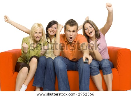 Three young woman and a man are sitting on the orange couch and looks like watching TV. Man is holding remote control. The're very excited by what they're see. Isolated on white in studio.