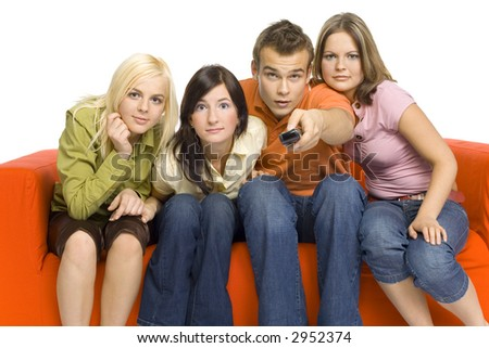 Three young woman and a man are sitting on the orange couch and looks like watching TV. Man is holding remote control. Something very interested happend on the screen. Isolated on white background. - stock photo