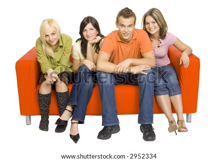 Three young woman and a man are sitting on the orange couch. They're looking at the camera. Isolated on white in studio. - stock photo