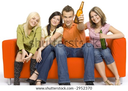 Three young woman and a man are sitting on the orange couch. Two of them are holding beer. Man's making toast. - stock photo