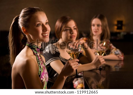 Three young woman in the nightclub are having fun and drink at the bar. Selective focus - stock photo
