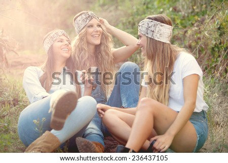 three young woman smiling in park at sunset - stock photo