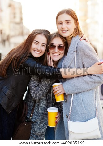 Three young women, best friends smiling at the camera - stock photo