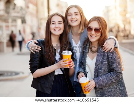 Three young women, best friends smiling at the camera. - stock photo