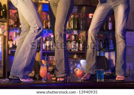 Three young women dancing on a bar counter - stock photo
