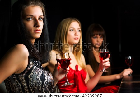 Three young women drinking red wine in a bar.