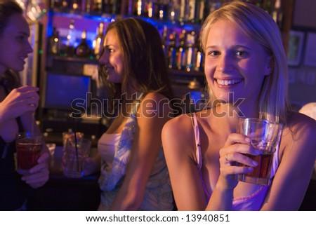 Three young women enjoying drinks at a nightclub - stock photo