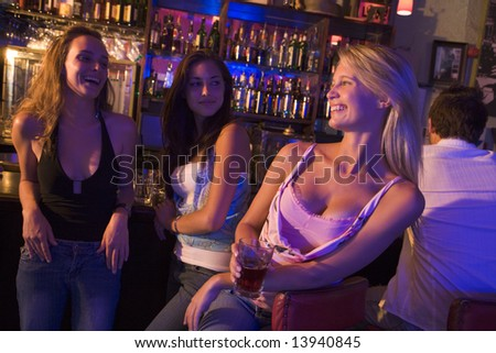 Three young women enjoying drinks together at a nightclub - stock photo