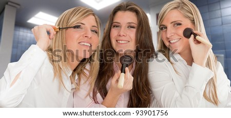 Three young women getting ready for going out, applying make-up - stock photo