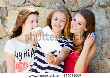 Three young women girl friends with different hair happy laughing at tablet blogging message - stock photo