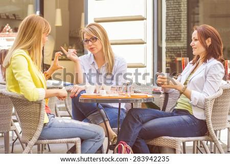 Three Young Women have Coffee Break Together in street cafe. Caucasian female relaxing on beautiful summer day in the city. - stock photo