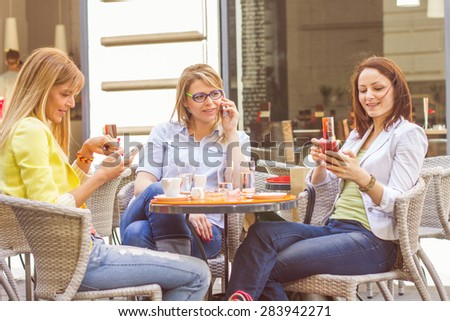 Three Young Women have Coffee Break Together in street cafe. Caucasian female using mobile phone. - stock photo