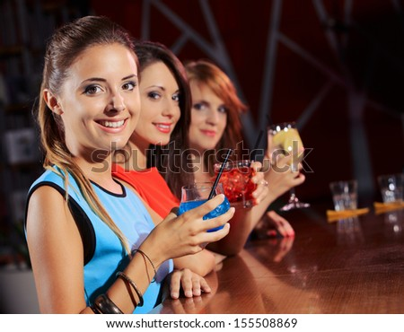 Three young women having a drink in a night club  - stock photo
