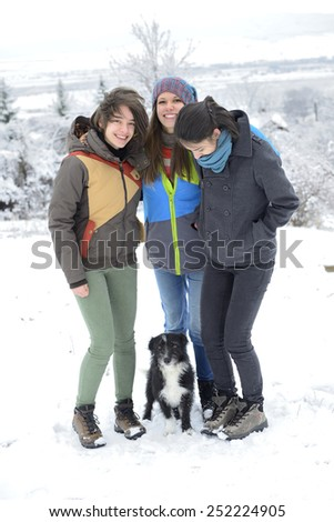 Three young women having having fun with small black dog outside in winter.  - stock photo