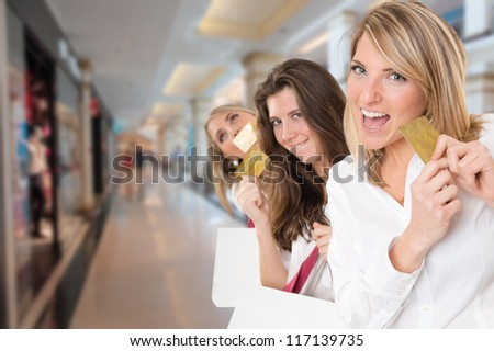 Three young women in a happy shopping expedition with credit cards - stock photo