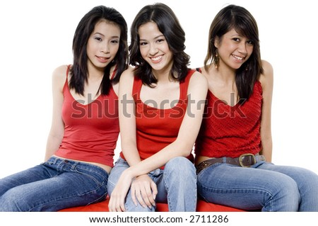 Three young women in red tops and jeans sitting on red seats