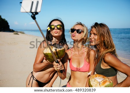 Three young women in swimsuit on the beach enjoying holidays and taking self portrait selfie stick. Group of female friends with coconuts taking selfie on the sea shore. Pout for a selfie on beach.