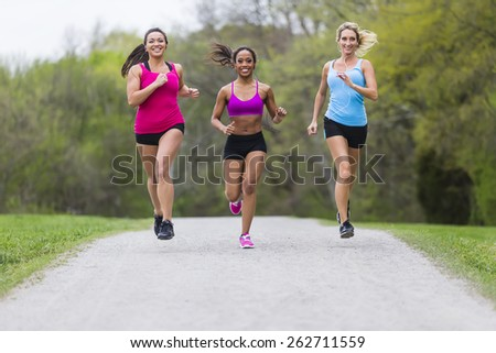 Three young women jogging in a park - stock photo