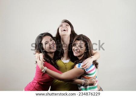 Three young women posing in the studio smiling as best friends - stock photo