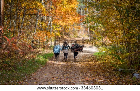 Three young women running up a country road in late October.
