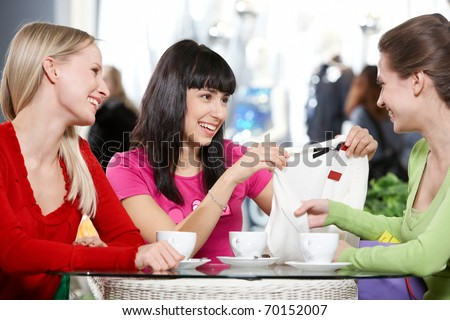 Three young women sitting in cafe and discussing new purchase - stock photo