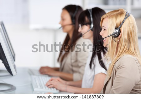 three young women sitting in the office using headset - stock photo