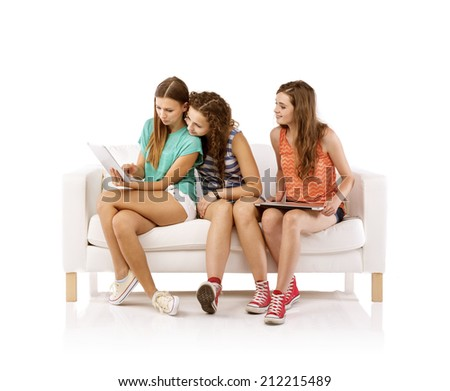 Three young women sitting on sofa and using digital tablet, isolated on white background. Best friends - stock photo
